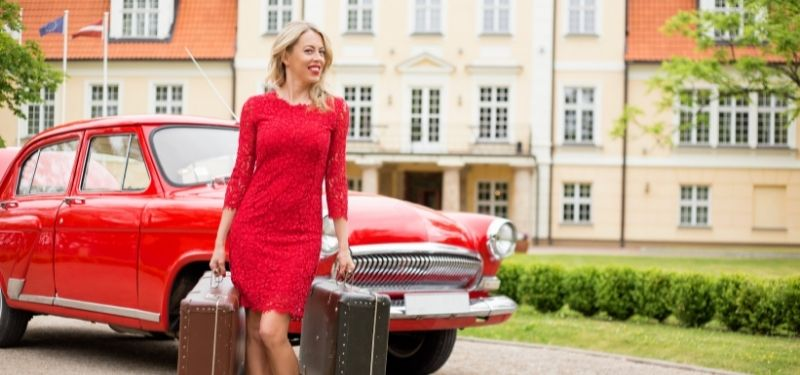 woman with suitcase and red car